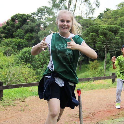 Menina correndo de uniforme verde